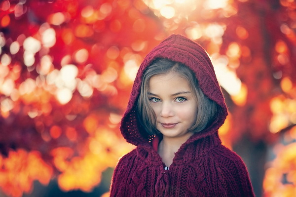 Little girl against colorful Autumn tree